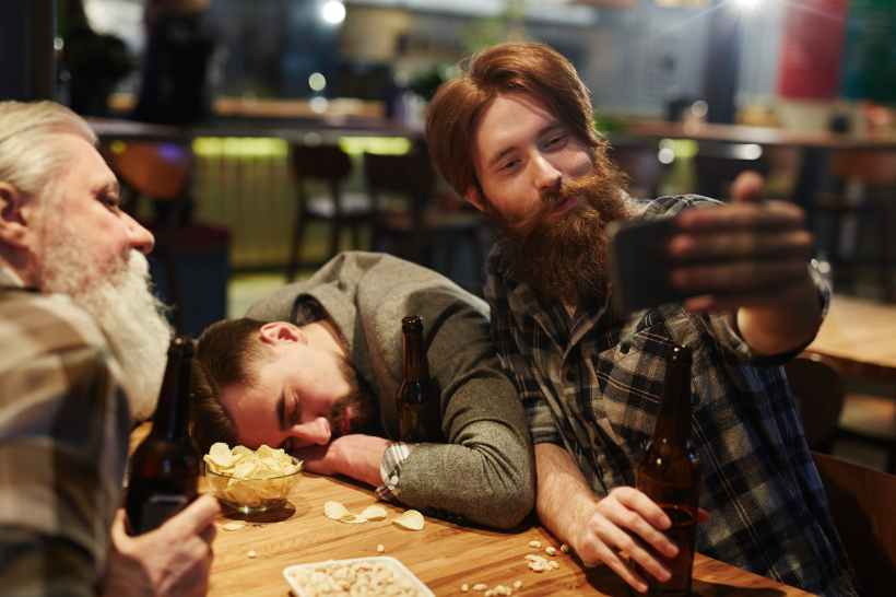 man taking a selfie with a drunk man
